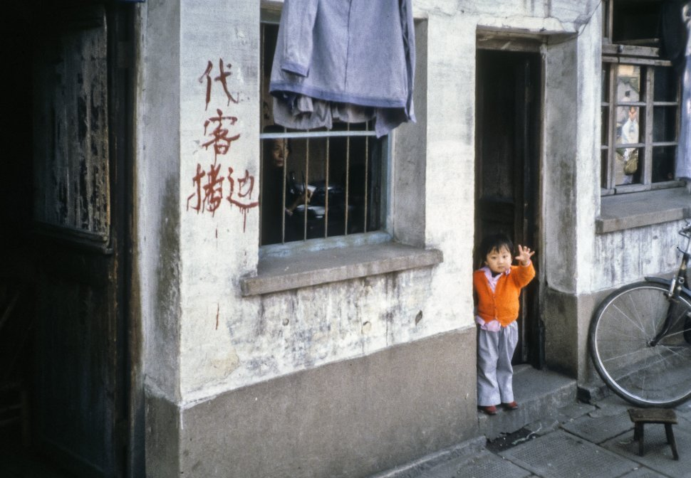 Free image of Child waving from a doorway at the camera, China