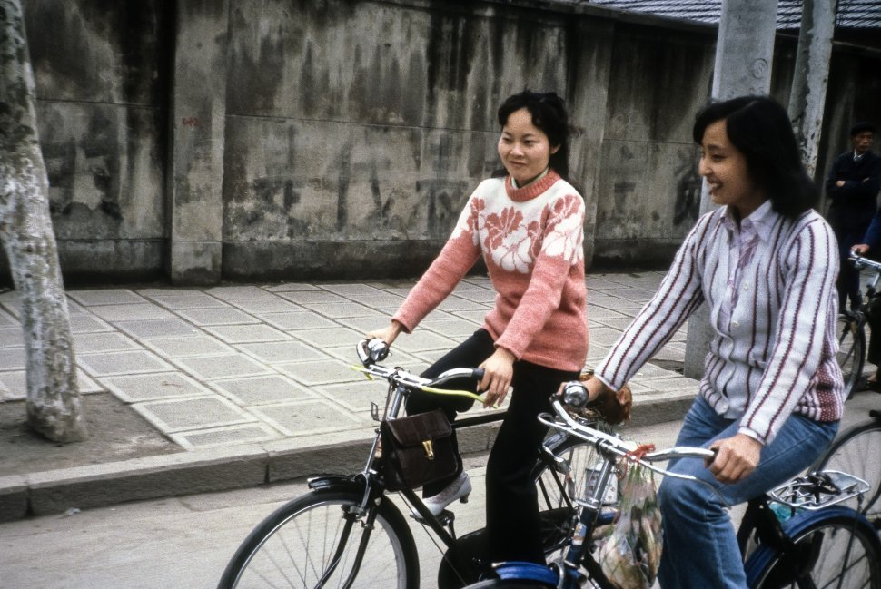 Free image of Two women riding their bicycles on the street, China