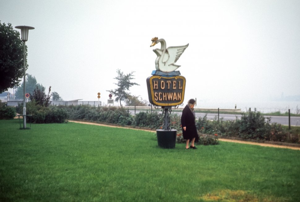 Free image of Woman below a sign for the Hotel Swan, Germany