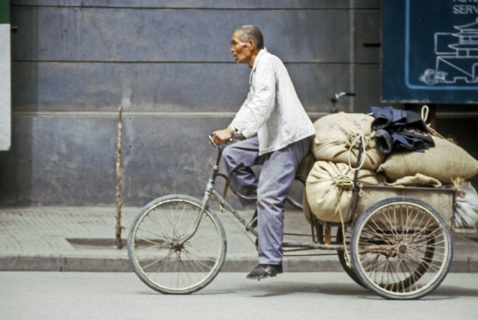 Free image of Man pulling a cart and sacks with his bicycle, China