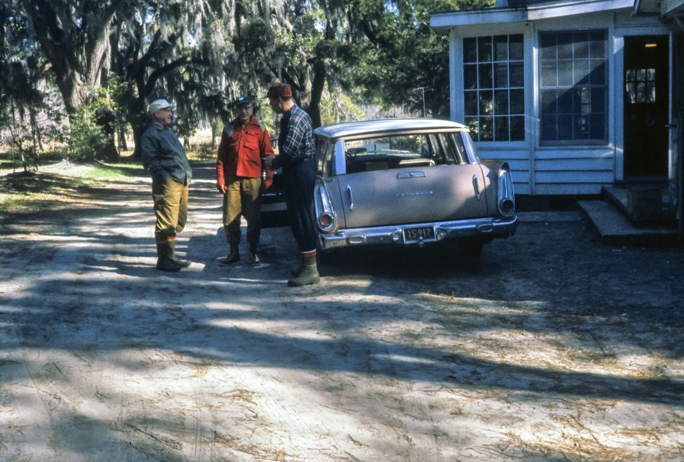 Free image of Men talking next to a home and station wagon in the swamp, USA
