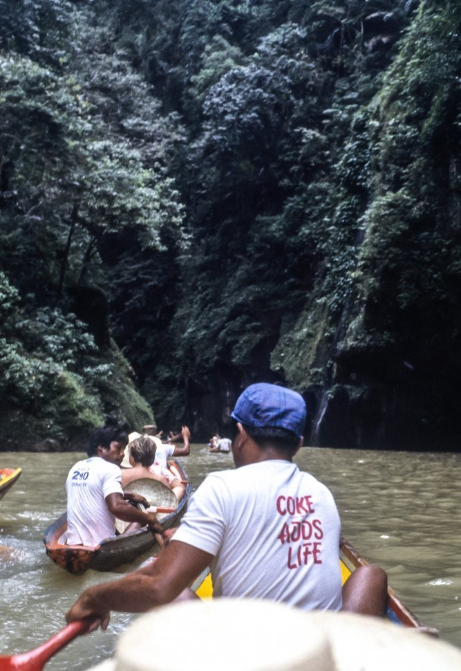 Free image of Tourists riding in small canoes, with guides, into a water cave.