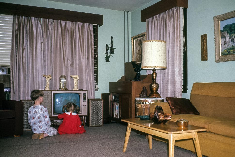 Free image of Children sitting too close to television in suburban living room, USA