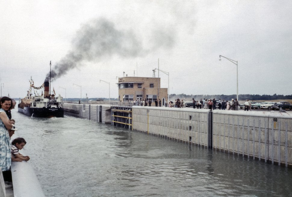 Free image of Crowd awaiting the arrival of a ship moving through a canal