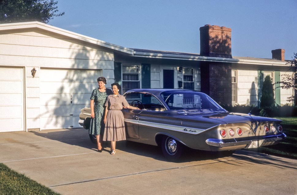Free image of Two women posing next to a vintage car in a suburban neighborhood, USA