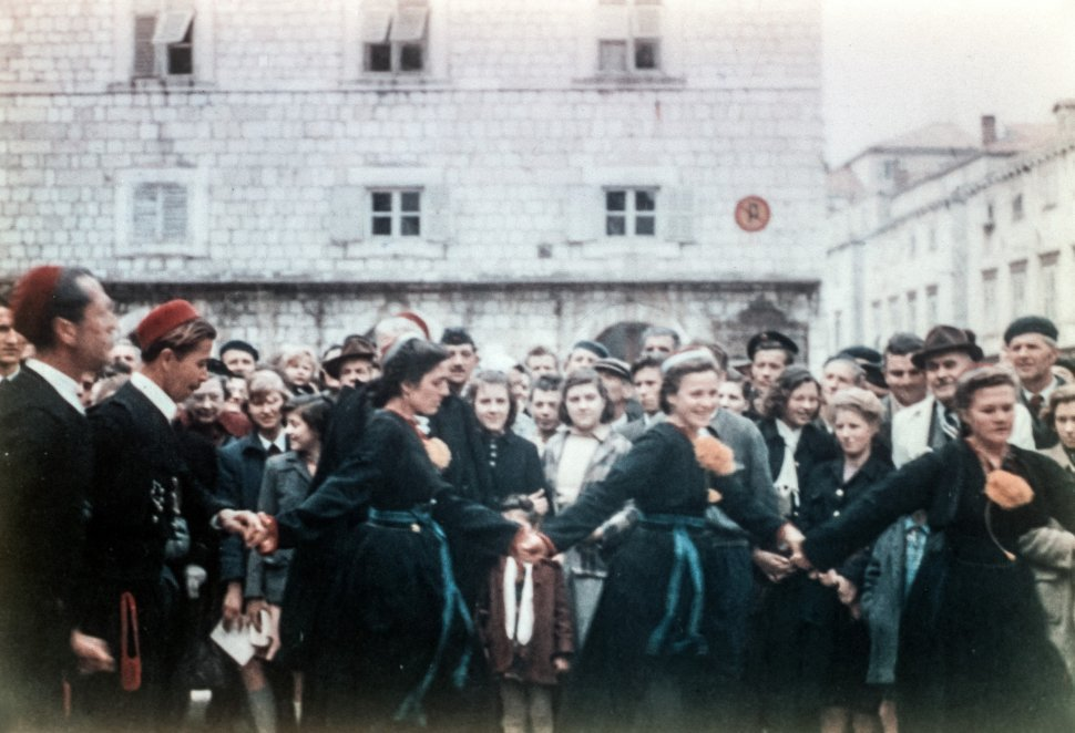 Free image of Women and men dancing in traditional costumes while a crowd watches, Europe