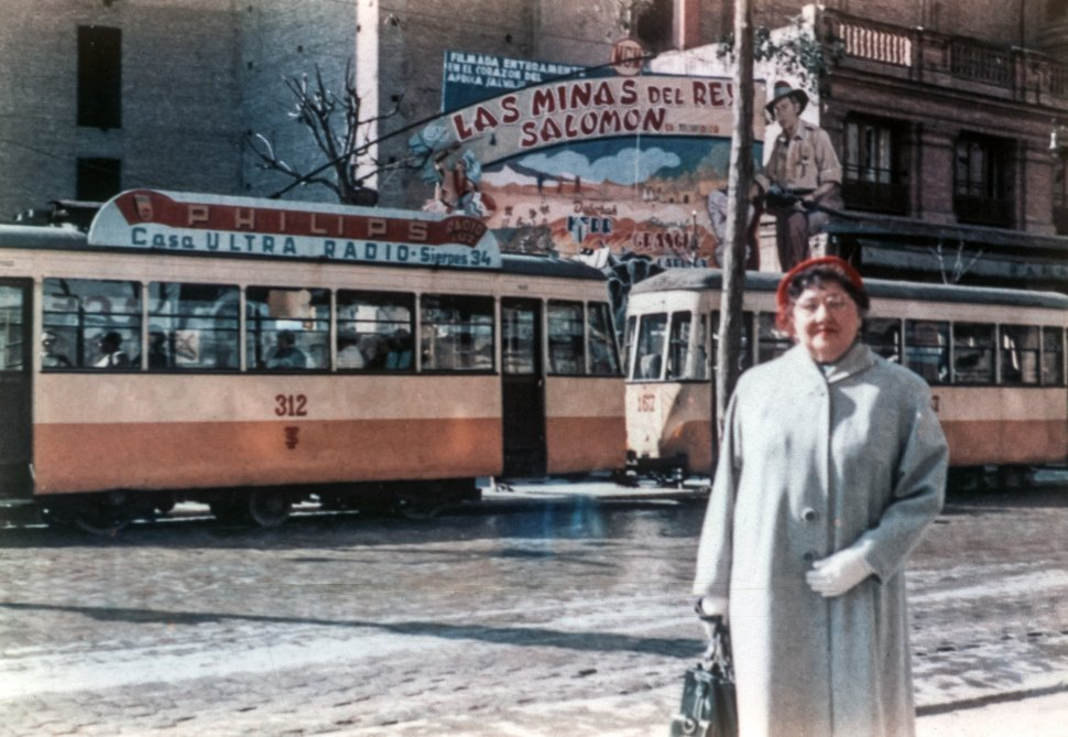 Free image of Portrait of a woman standing on the street in front of trolley cars.