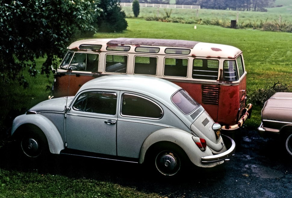 Free image of Volkswagen car and bus parked next to each other in a muddy parking lot.