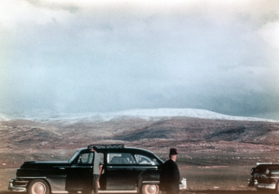Free image of Two antique cars parked on the winter tundra.