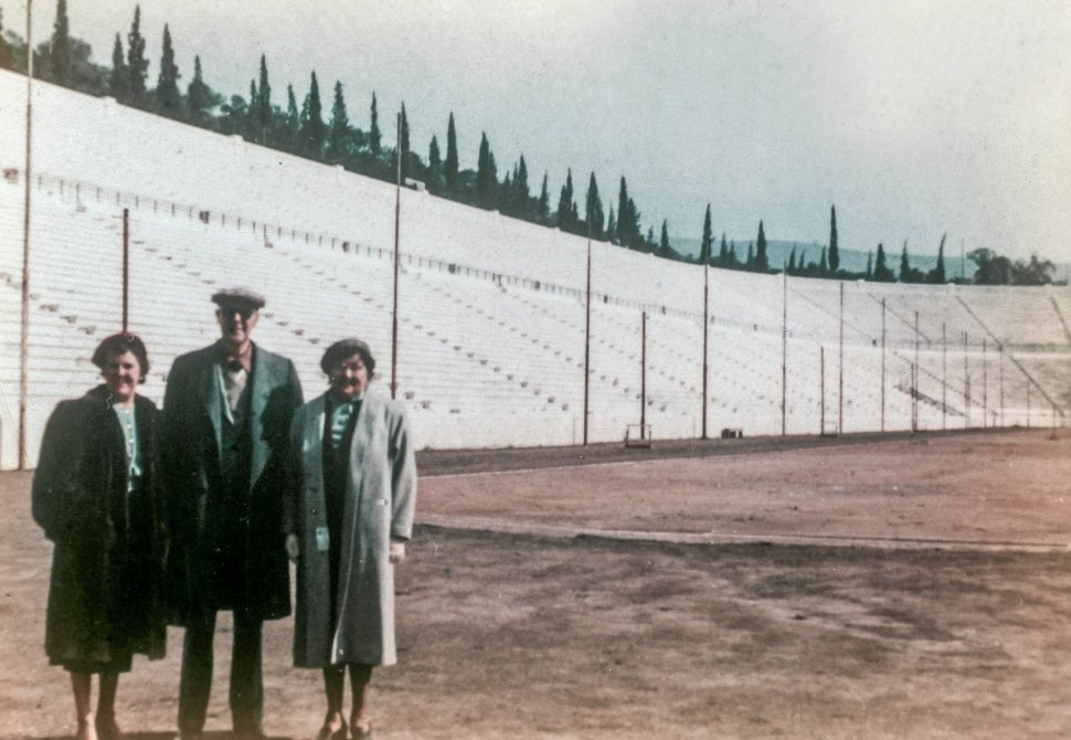 Free image of Three people posing for a portrait in a large empty stadium.