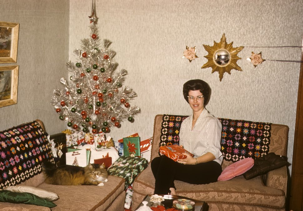 Free image of Woman posing for picture with Christmas gift, USA