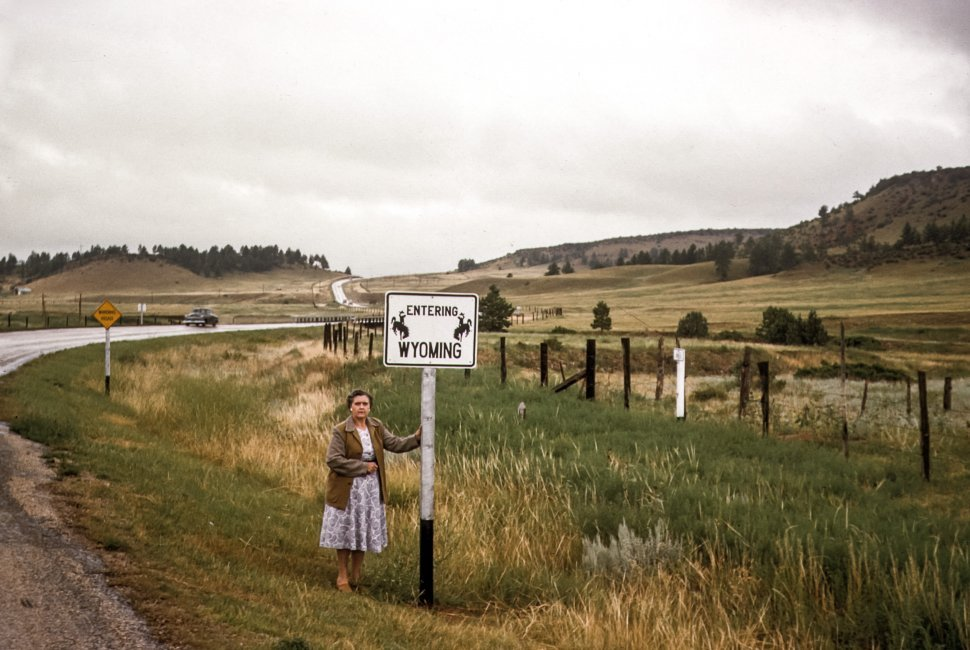 Free image of Woman posing in front of Wyoming border sign, USA