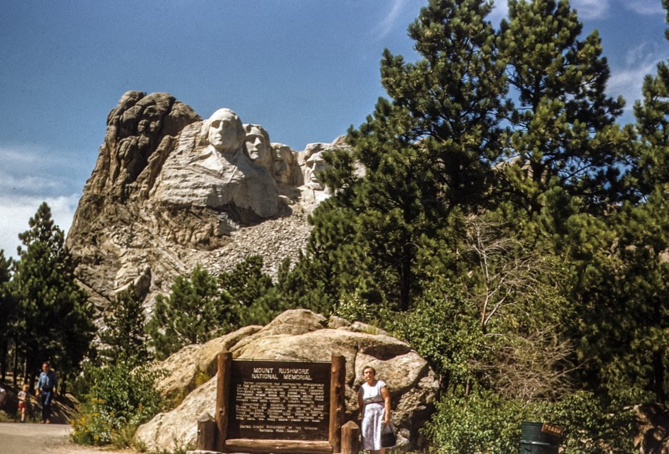 Free image of Woman posing under stone carvings of George Washington, Thomas Jefferson, Theodore Roosevelt and Abraham Lincoln, Mount Rushmore, South Dakota, USA