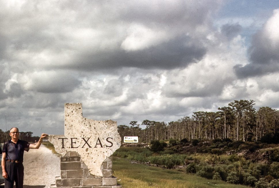 Free image of Man standing next to state sign, Texas, USA