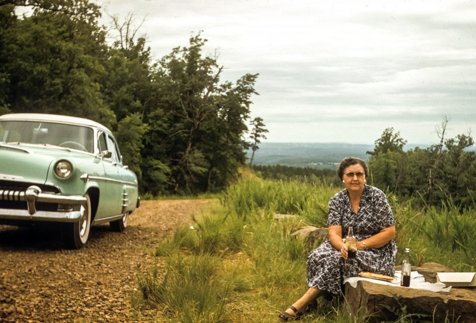 Free image of Woman enjoying picnic next to vintage car, USA