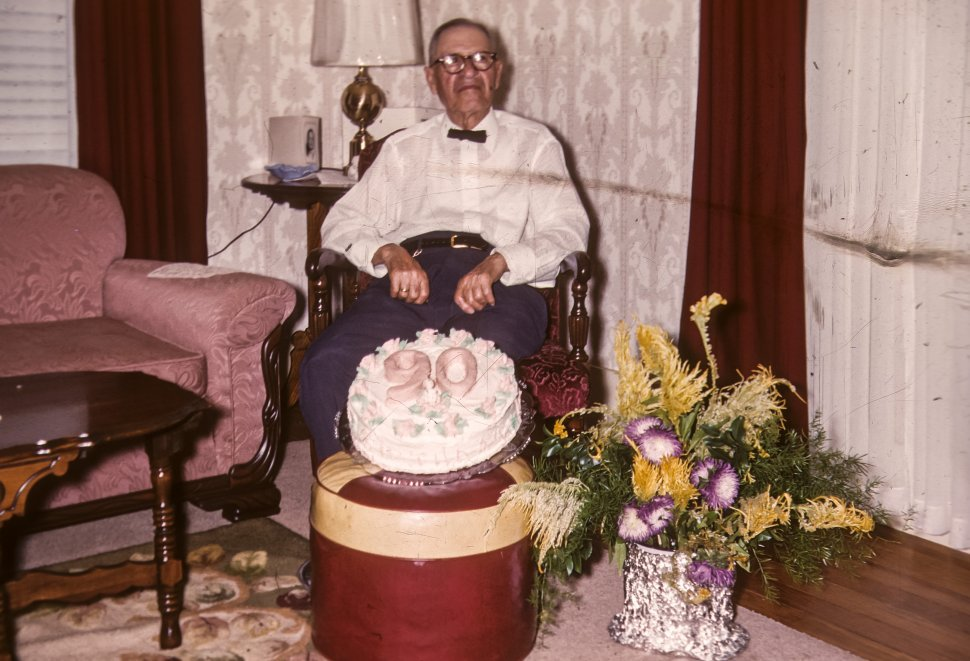 Free image of Portrait of a man posing in a chair with his 90th birthday cake in front, USA