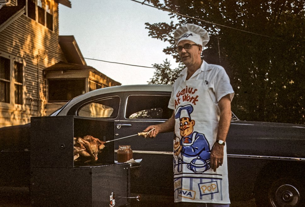 Free image of Man posing while cooking chicken on a barbecue, USA