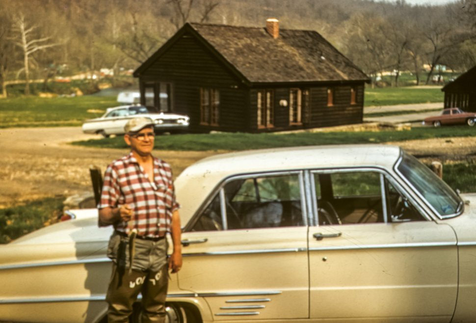 Free image of Man posing with fish next to a vintage car and cabins, USA