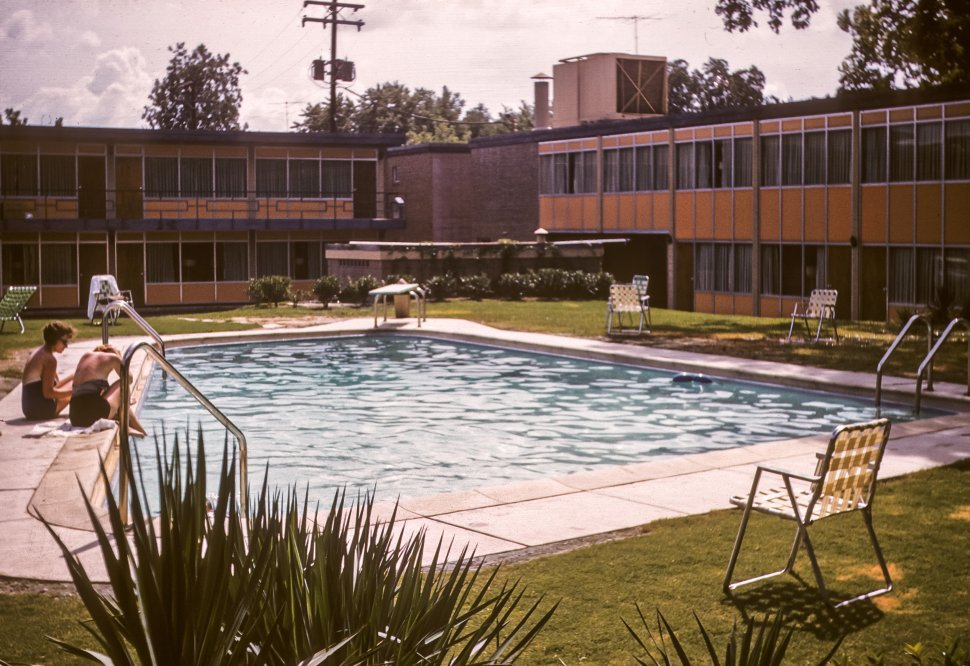 Free image of Motel pool area with tourists sitting and talking, USA