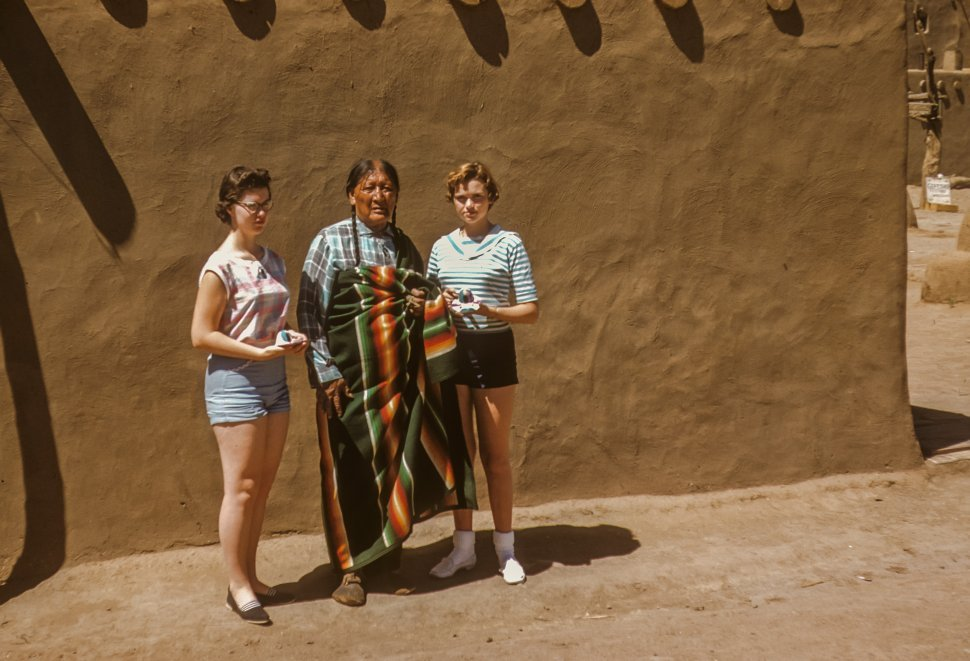 Free image of Two female tourists posing with a Native America man, USA