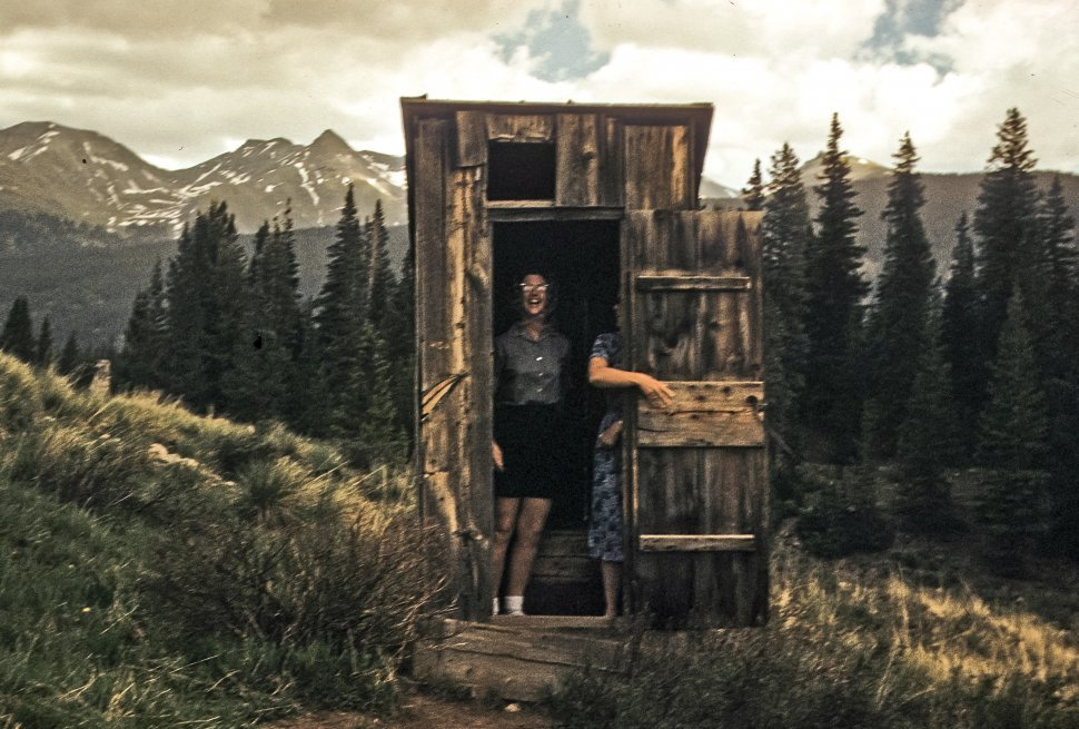 Free image of Humorous image of two women posing in an old outhouse, USA