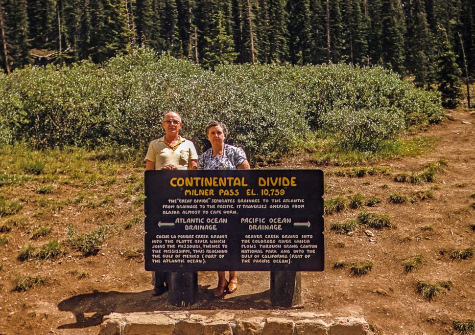 Free image of Couple posing with the sign for the Milner Pass at the Continental Divide, Colorado, USA