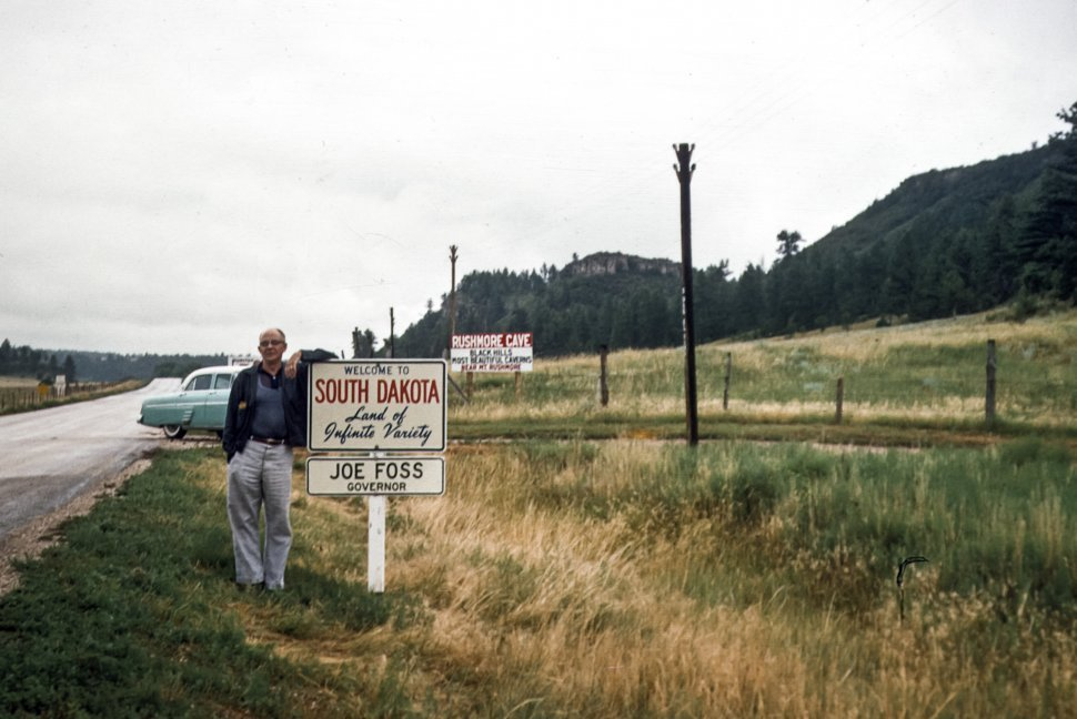 Free image of Man posing next to the state line sign , South Dakota, USA
