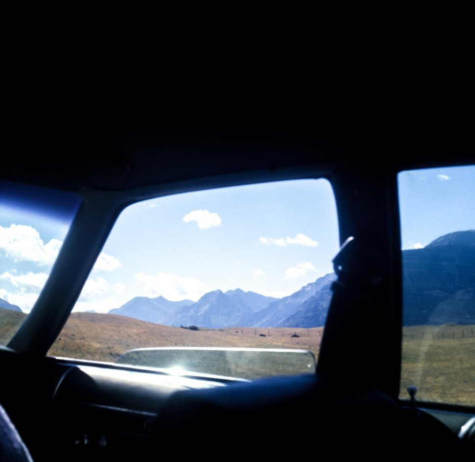Free image of Mountain peaks through a car window while driving, USA