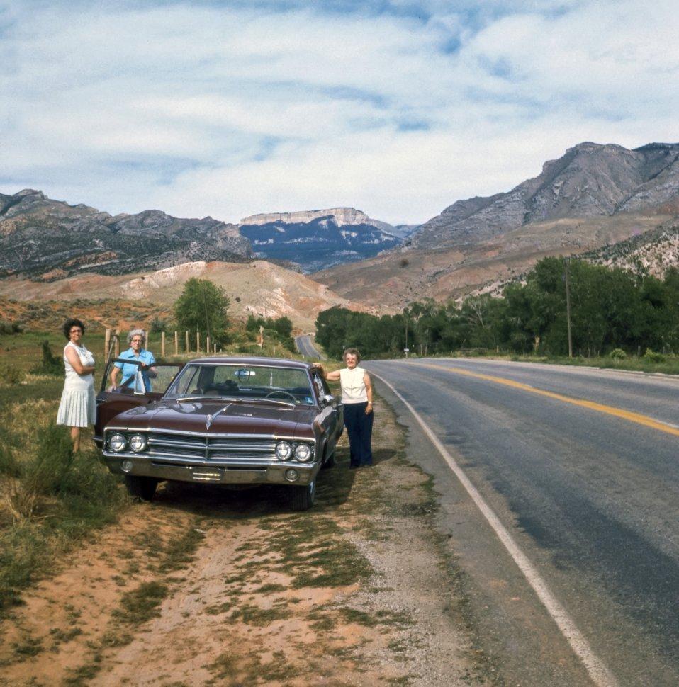 Free image of Three women posing roadisde next to their car below a mountain, USA