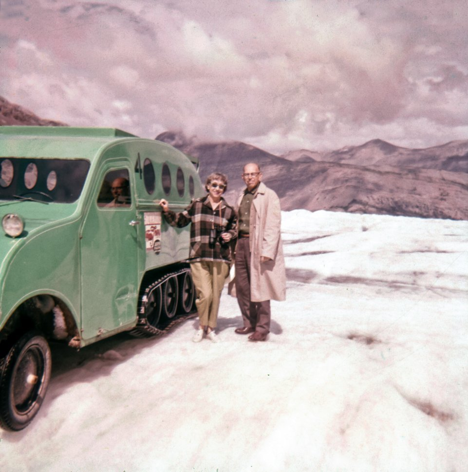 Free image of Couple posing next to a half-track vehicle on a snow capped mountain, Canada