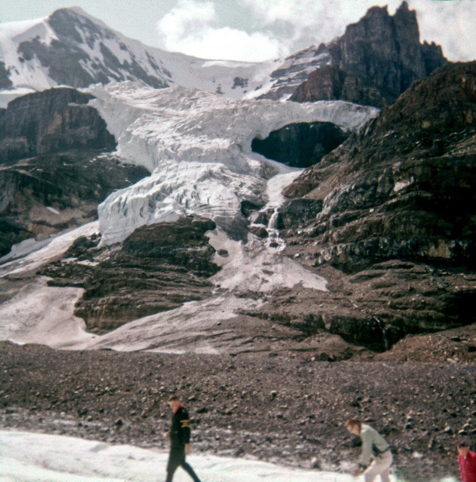 Free image of Visitors moving up the mountain side in front of a glacier.