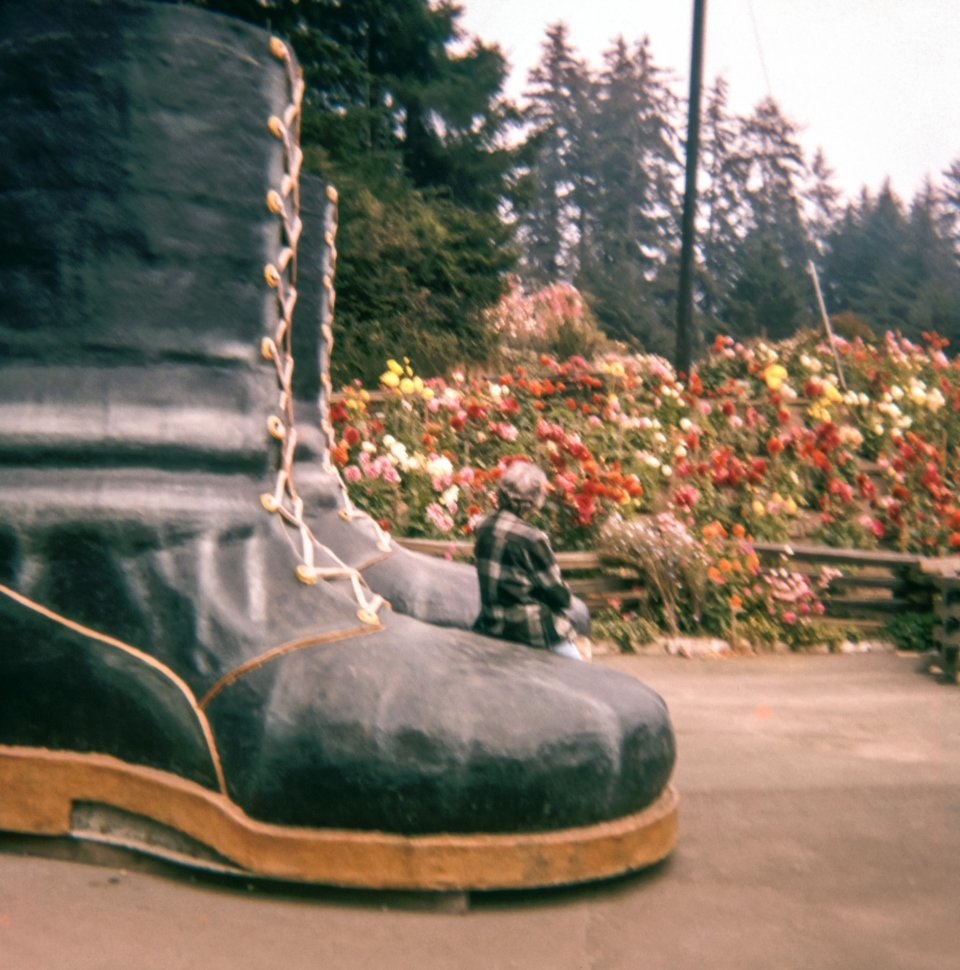 Free image of Woman sitting next to a pair of giant Paul Bunyan boots in a theme park in Klamath, California.
