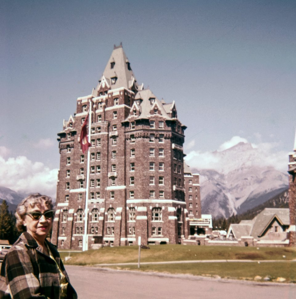 Free image of Woman posing in front of a mountain hotel, Europe