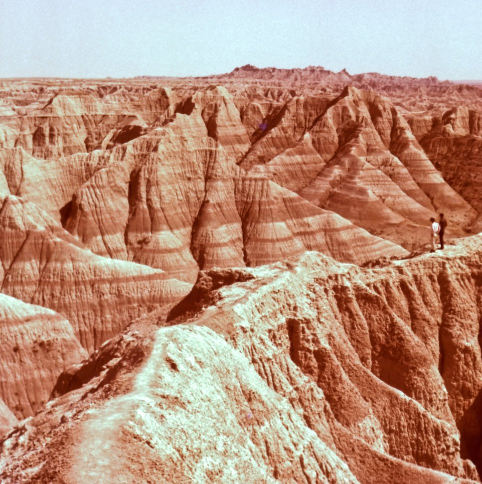 Free image of Two men observing the sandstone canyons and formations Badlands National Monument, South Dakota, USA
