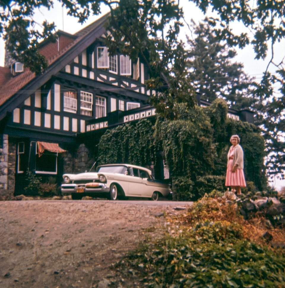 Free image of Woman posing next to a vintage car and a home or hotel, USA