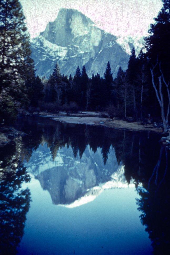 Free image of Mountain peak reflected in still lake water.