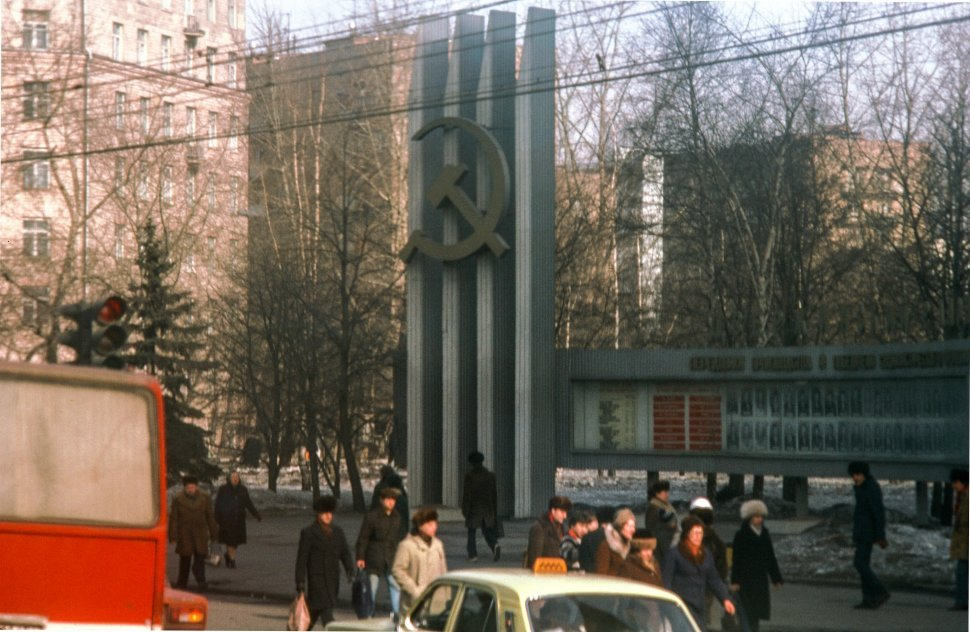 Free image of People walking besides,the soviet hammer and sickle monument in U.S.S.R