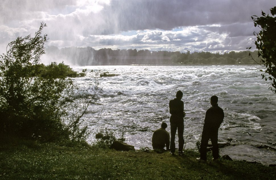 Free image of People looking at Niagara Falls during sunset - New York
