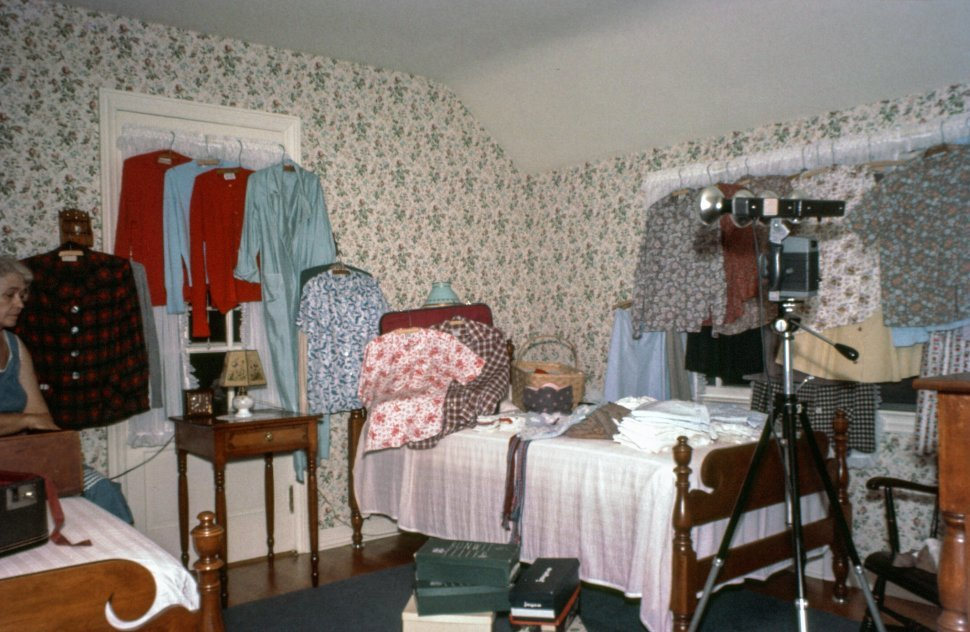 Free image of Woman sitting on bed as clothes hanging around the room