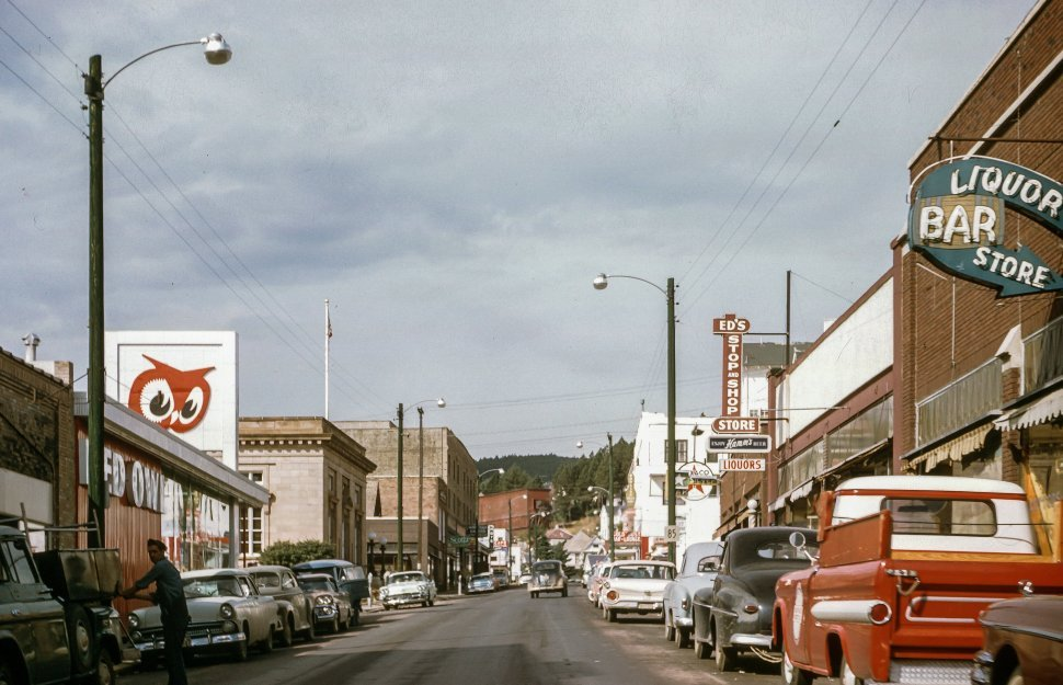 Free image of Small businesses and shops along street in 1950s.