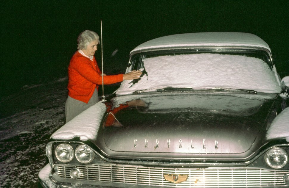 Free image of Woman cleaning the snow from car front glass