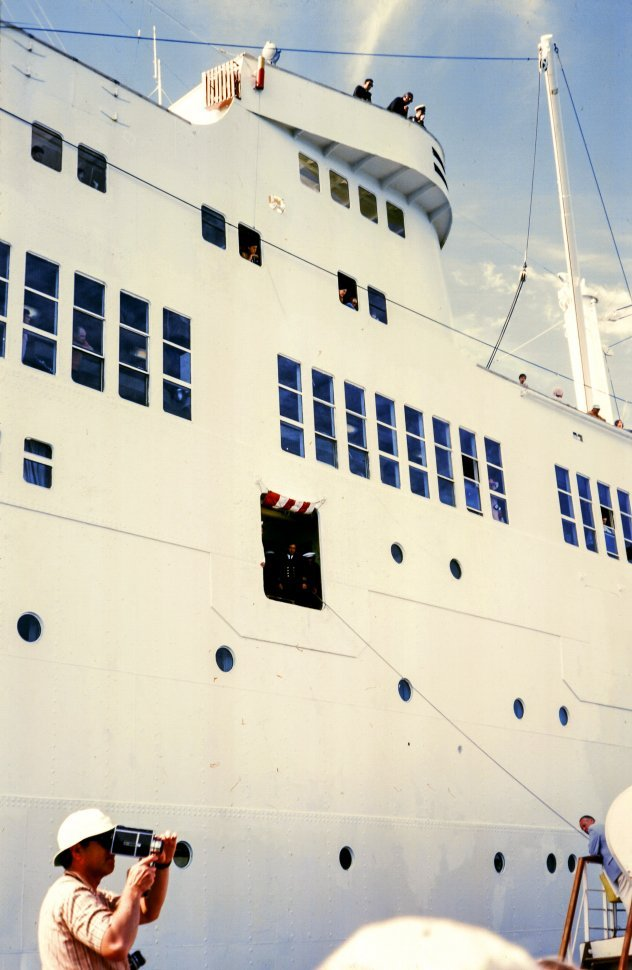 Free image of Low Angle view of a large ship as one man making a video