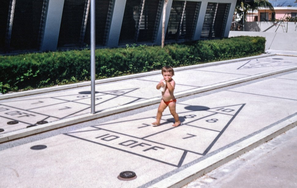 Free image of One-year-old child playing outside in a swimming costume