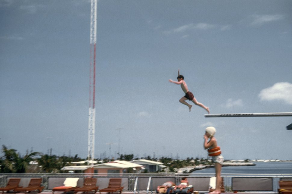 Free image of Children jump into the swimming pool from diving board