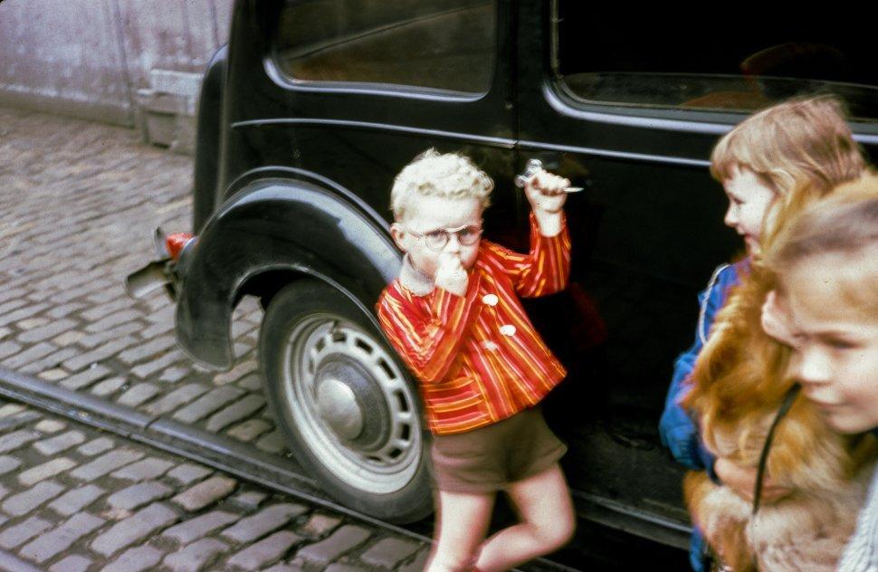 Free image of Three Child Standing near black car on the street
