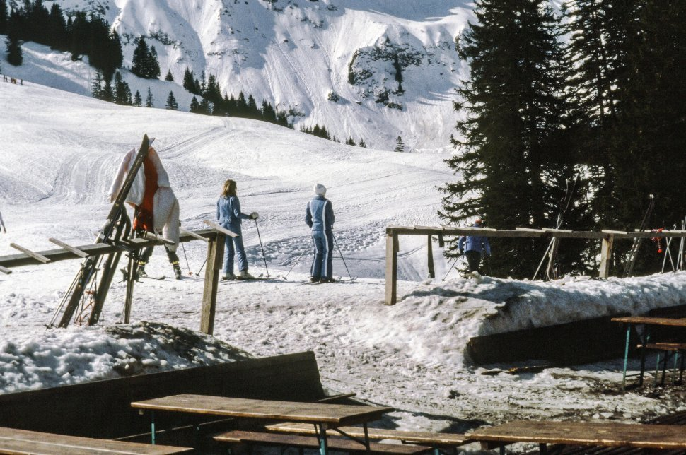 Free image of Two skiers skiing in the snow at the base of a run