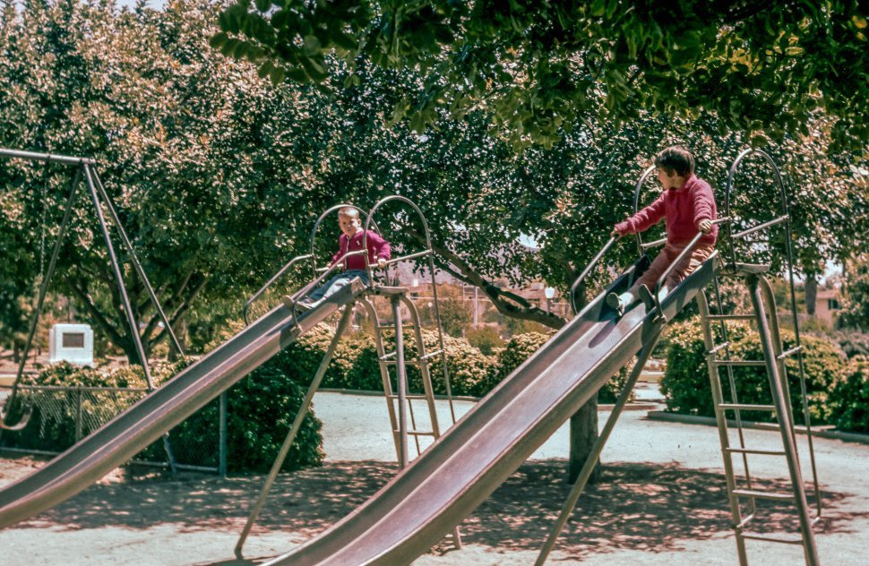 Free image of Children Playing on two slides near swingset in the park