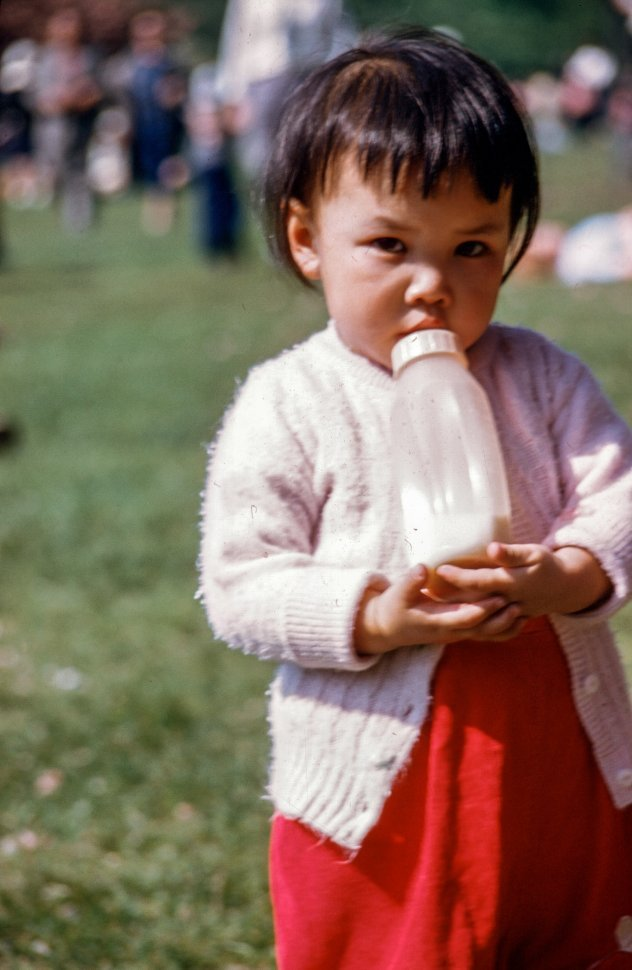 Free image of One-year-old girl drinking milk from her bottle