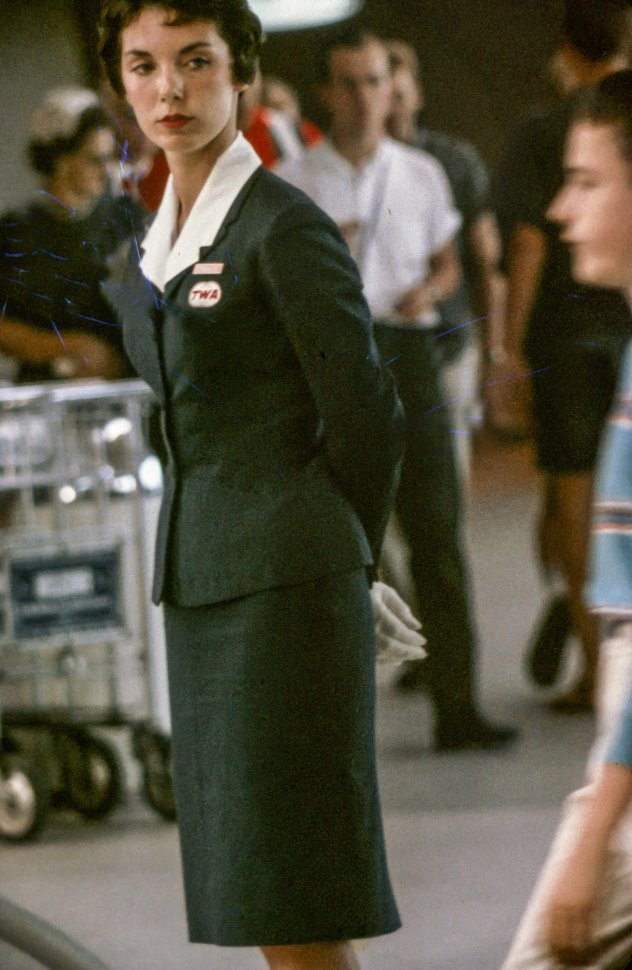 Free image of TWA flight attendand observes passengers at the airport