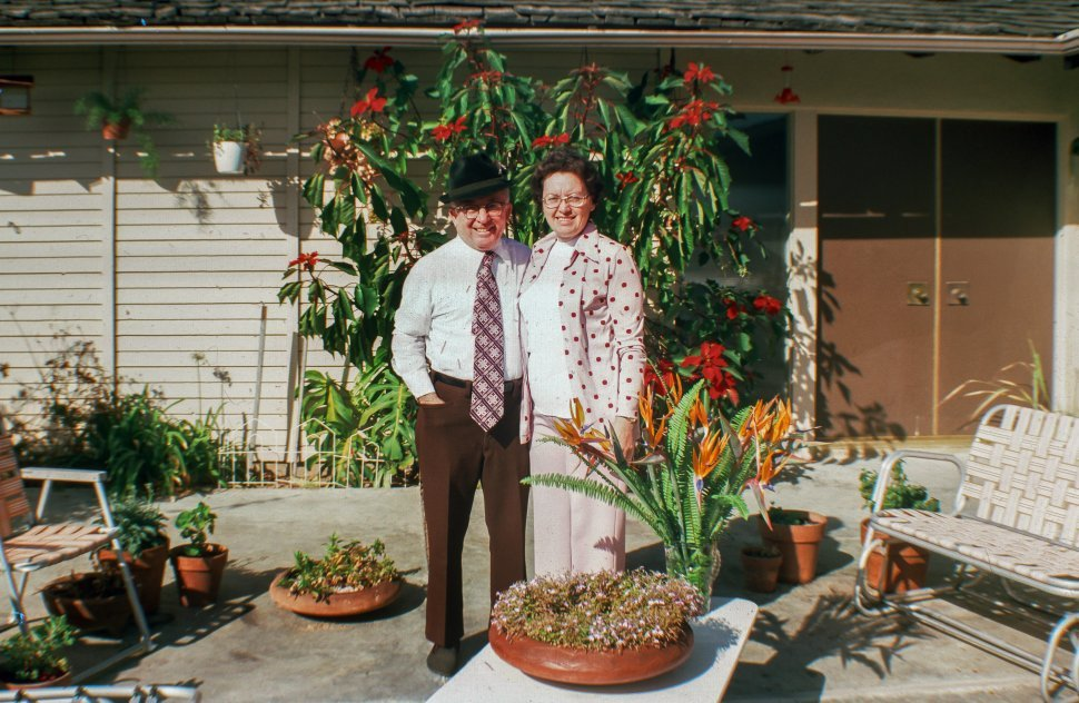Free image of Well dressed couple posing outside their house